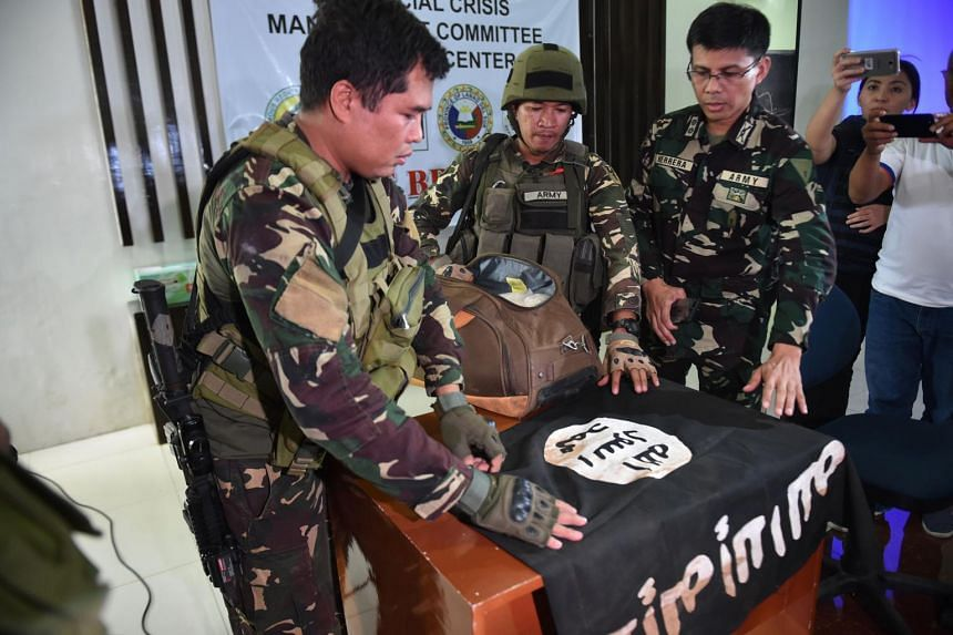 Philippine Army troopers prepare to display an ISIS flag that was recovered from an Islamist militants' position.
