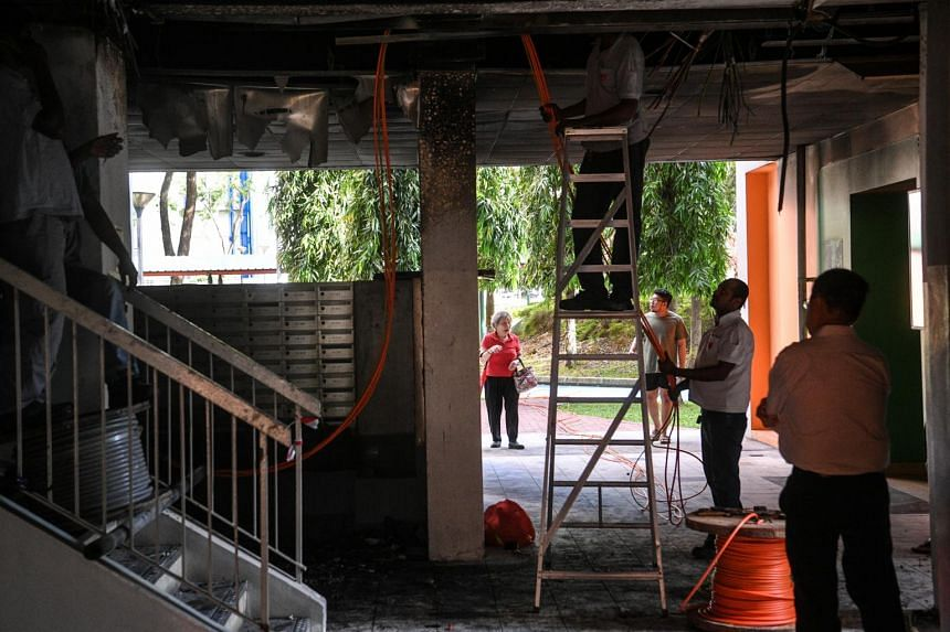 Workers replace electrical cables at the void deck of Block 14A in Lorong 7 Toa Payoh, on June 20, 2017.