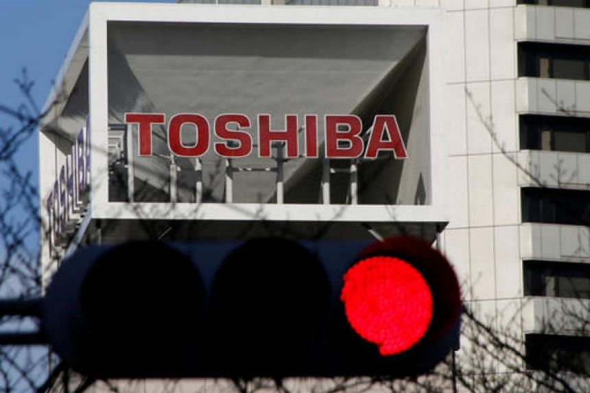 The logo of Toshiba Corp is seen behind a traffic signal at its headquarters in Tokyo.