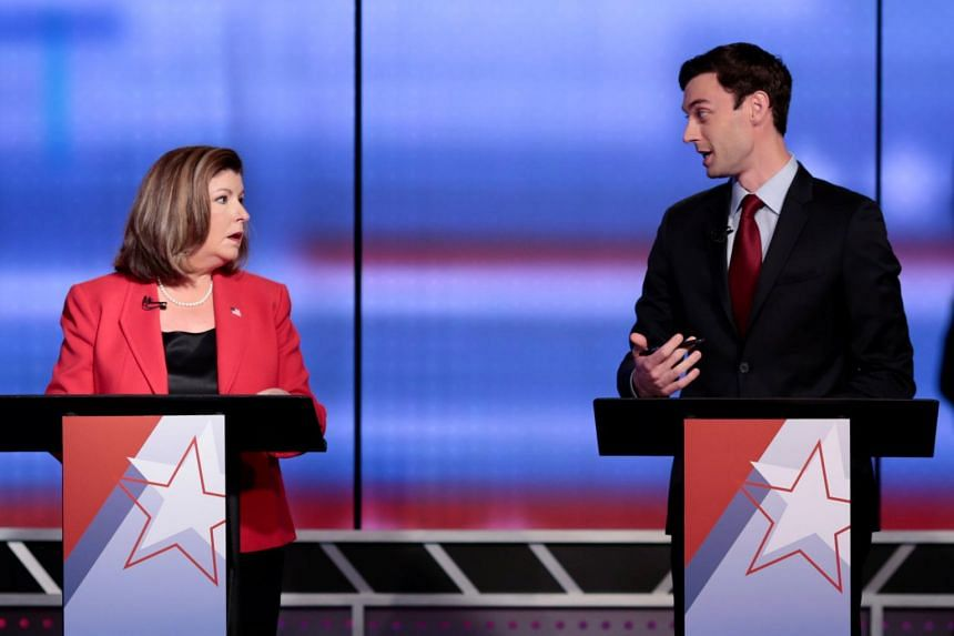 Republican candidate Karen Handel (left) and Democratic candidate Jon Ossoff (right) exchange words moments before Georgia's 6th Congressional District special election debate at WSB-TV studios in Atlanta, Georgia.