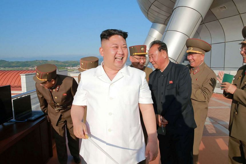 North Korean leader Kim Jong Un (centre) inspecting a test-fire of a new-type of ground-to-sea cruise rocket.