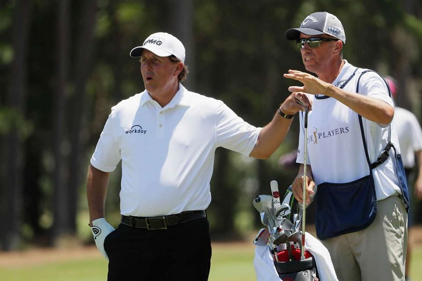 Phil Mickelson lines up a drive with his caddie Jim Mackay.