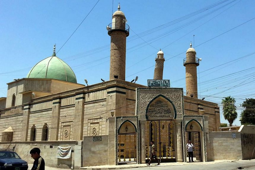 People walk in front of the mosque in Mosul, in July 2014.