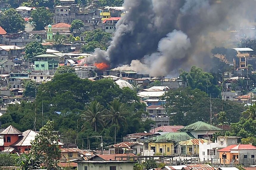 Smoke billows from burning buildings in Marawi on the southern island of Mindanao on June 18, 2017, after Philippine Airforce planes pounded Islamist militants' positions.