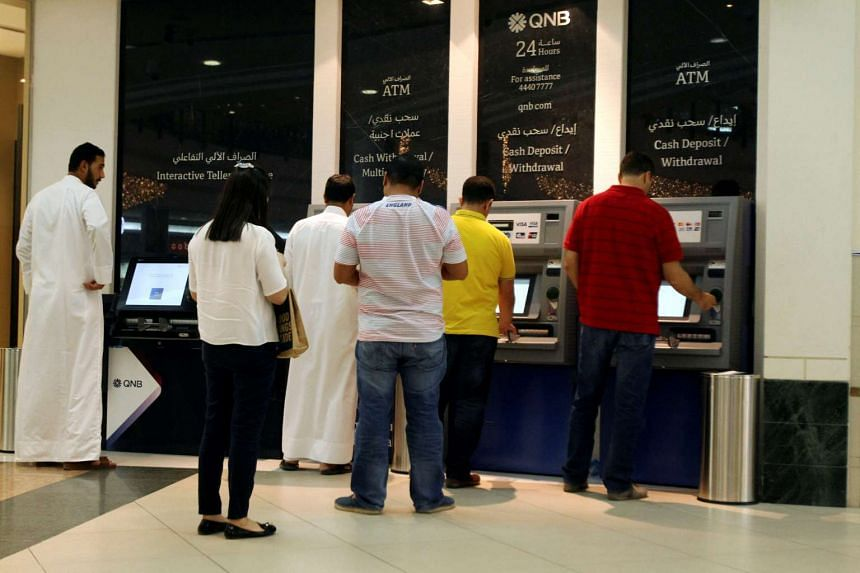 People use ATM machines at Qatar National Bank in Doha, Qatar, June 13, 2017.