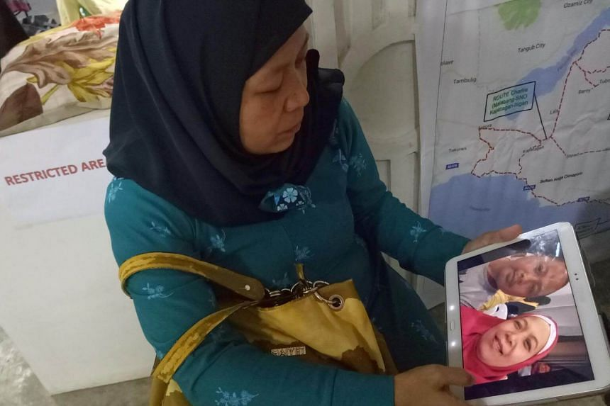 Carmalia Baunto,42, shows an image of herself and her husband, Nixon Baunto, who is trapped inside the besieged town of Marawi City, Philippines, on June 21, 2017.