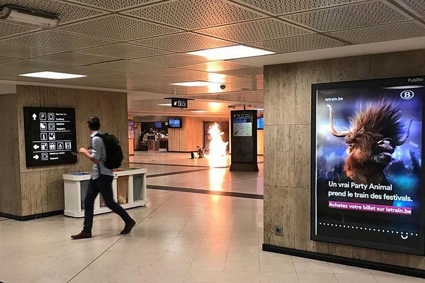 """The bag holding a bomb caught fire after the device """"partially exploded"""" at a train station in Brussels, Belgium, on Tuesday. The suspect, who had dropped the bag, was later shot dead by a soldier on patrol."""
