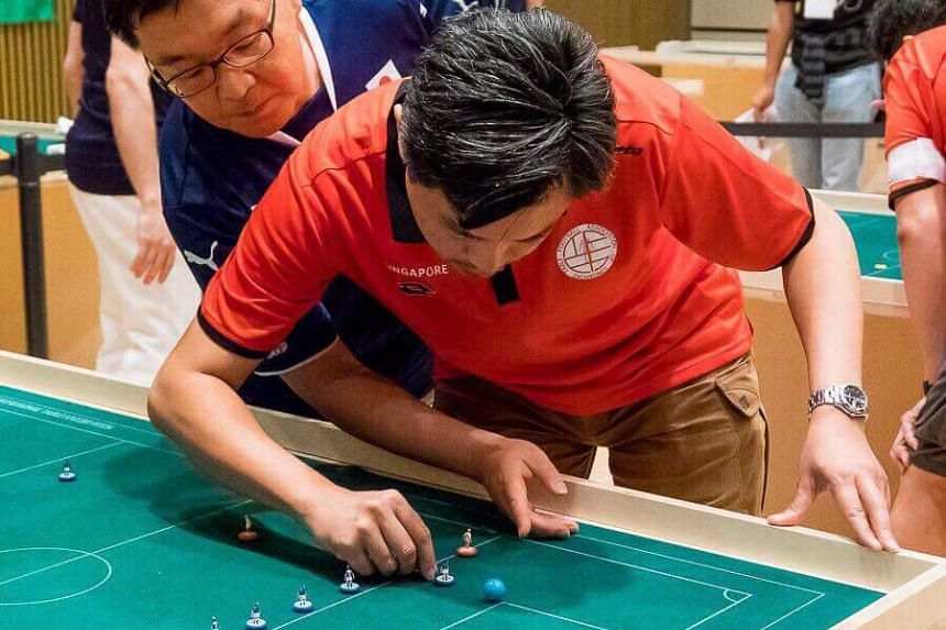 Japan's Kenzo Koi (in blue) and Singapore's John Ho (in red) battling it out at the Asian Cup in sports table football in Tokyo on June 10, 2017.