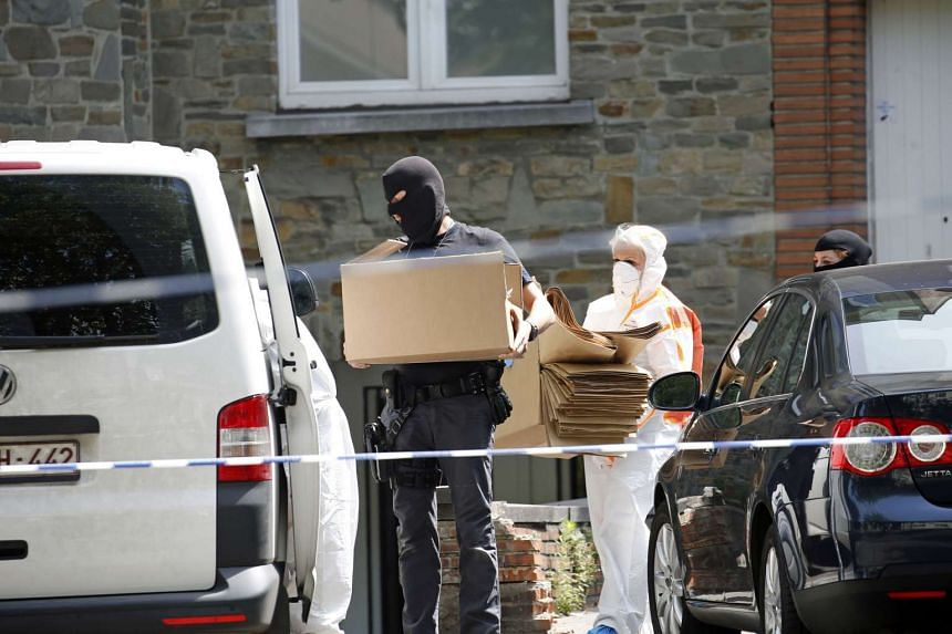 Forensic police carry boxes as they search the house of the suspected bomber in Molenbeek.