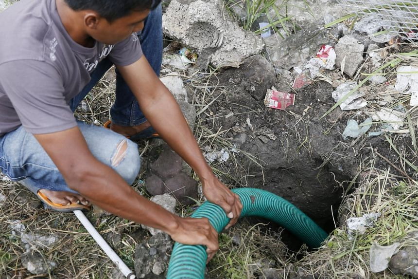 An Indonesian worker draining a tunnel, which was reportedly used by four foreign prisoners to escape from Bali's Kerokoban Prison on June 19, 2017.