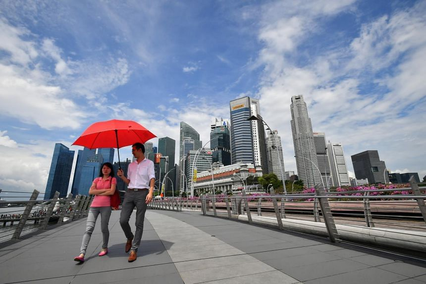 People walking on the Jubilee Bridge with the skyline of Central Business District in the background.