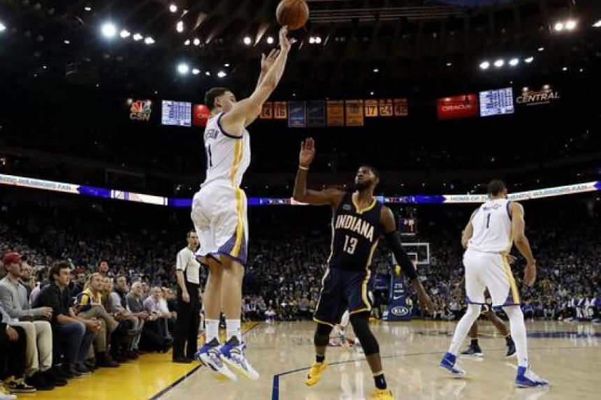 Indiana Pacers forward Paul George (centre) trying to defend as Golden State Warriors guard Klay Thompson shoots a three-pointer at the Oracle Arena in Oakland, California.