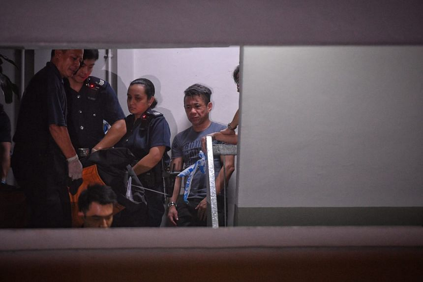 An unidentified man reacts as the second body is taken away from the unit.