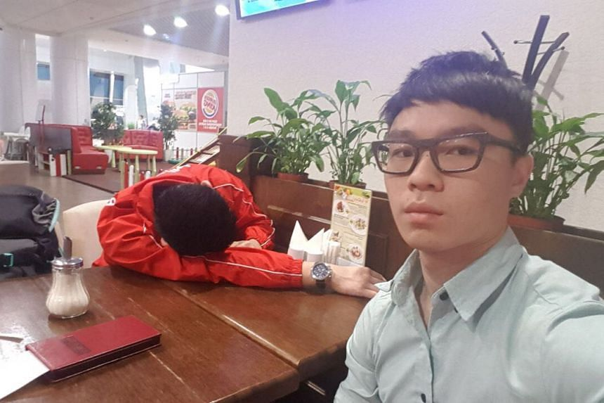 Powerlifter Matthew Yap (left) sleeps at a cafe in Minsk airport while brother Marcus keeps watch on June 22, 2017.