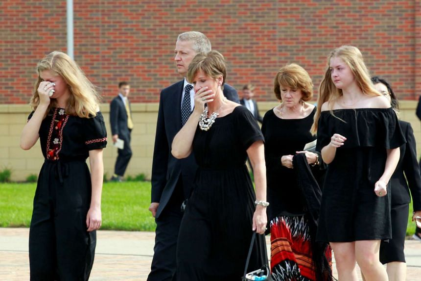 Mourners console one another as the hearse carrying Otto Warmbier departs for the cemetery after the service.