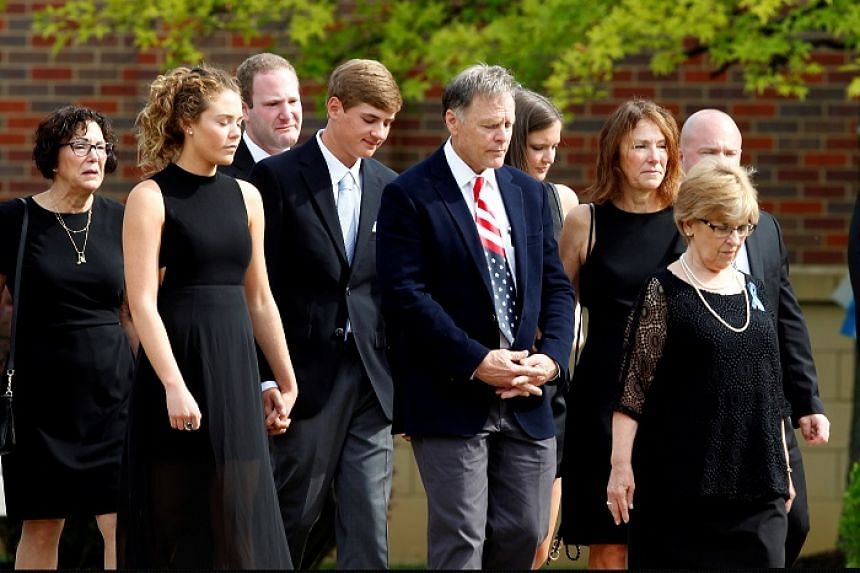 The family of Otto Warmbier follow his casket to the hearse after the funeral service.