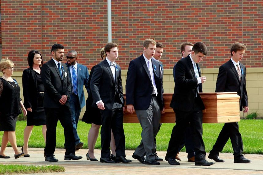 The casket of Otto Warmbier is carried to the hearse followed by his family and friends after the funeral service.