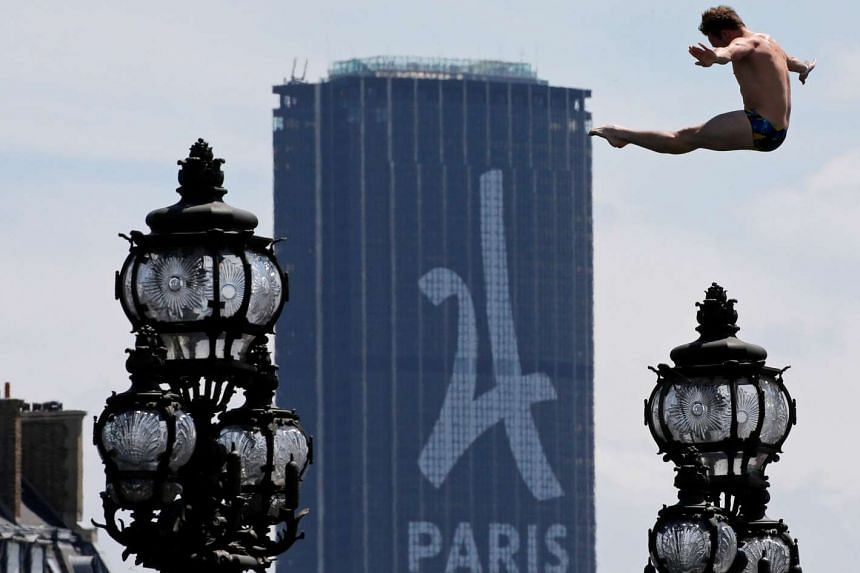 A diver jumping off a platform near the Alexander III bridge into the River Seine with the Montparnasse tower in the background on June 23, 2017, as Paris transforms into a giant Olympic park to spur its 2024 bid.