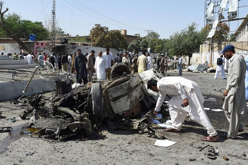 Pakistani security officials inspect the site of a powerful explosion that targeted a police vehicle in Quetta on June 23, 2017.