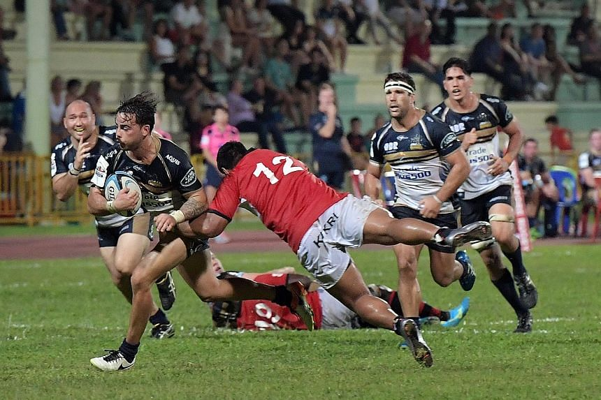 Former delivery man Andrew Muirhead of the Australian Super Rugby team Brumbies shrugs off a tackle en route to scoring a try against the Asia Pacific Dragons yesterday. The Brumbies beat the Dragons, an invitational side made up of top players from