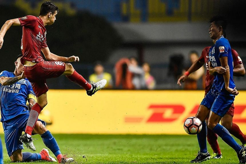 Shanghai SIPG midfielder Oscar kicking the ball in the direction of a Guangzhou opponent. His actions sparked a brawl during the Chinese Super League match last Sunday.