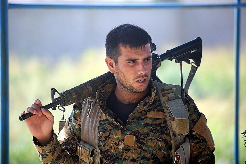 A member of the Kurdish YPG in the Syrian city of Raqqa on Wednesday, during an offensive by the US-backed fighters to capture ISIS' de facto Syrian capital. The US has told Turkey that weapons provided to the YPG in Syria would be taken back once IS