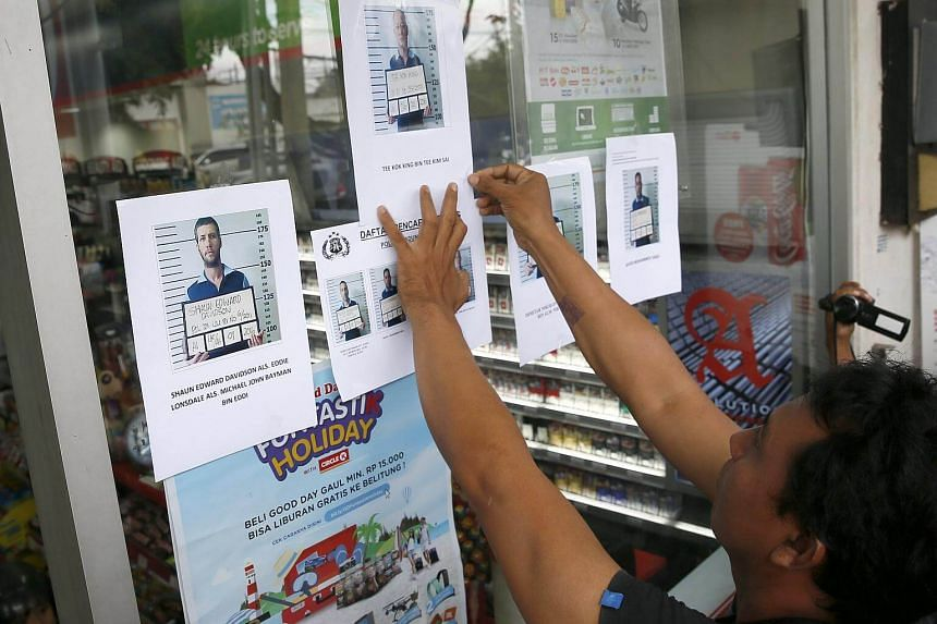 An Indonesian Police officer attaches photographs of four foreign prisoners who escaped from Bali's Kerokoban Prison at a convenient store in Bali.