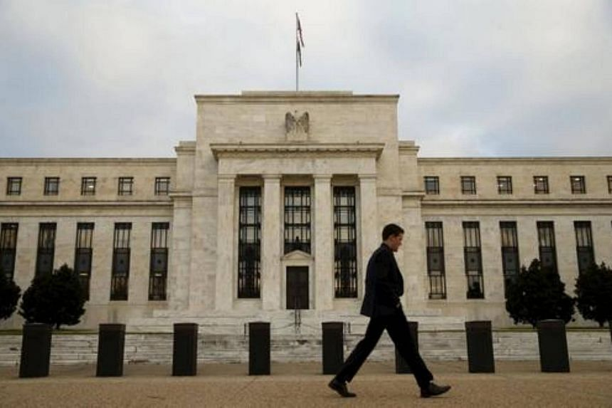 A man walks past the Federal Reserve building in Washington.