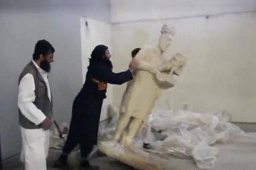 Men attacking artefacts, some of them identified as antiquities from the 7th century BC, with sledgehammers and drills, saying they were symbols of idolatry.