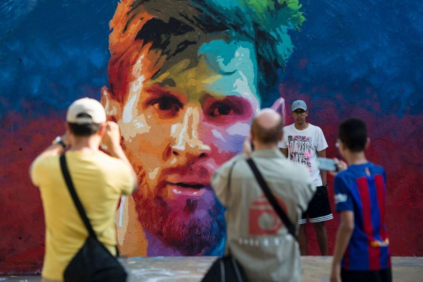 People taking photos of graffiti portraying Argentinian forward Lionel Messi on June 17, 2017 in Barcelona.