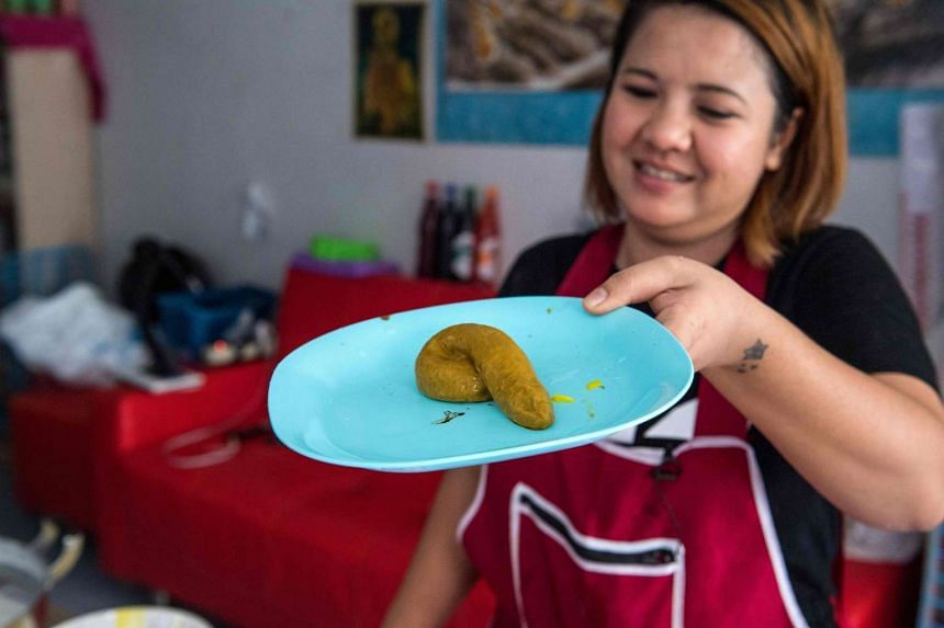 Wilaiwan Mee-Nguen shows off a dessert in the shape of dog poop that she prepared at her home in Bangkok on June 19, 2017.