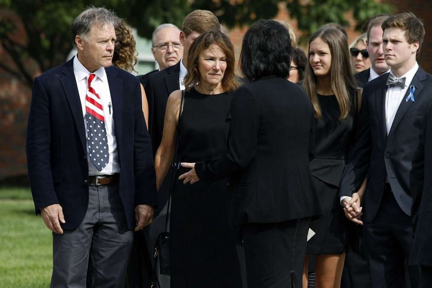 Fred and Cindy Warmbier talk with a woman after watching the casket of their son Otto carried out from the service.