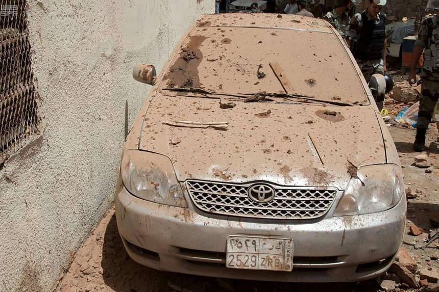 A damaged car is seen as Saudi officials inspect the scene of a foiled terrorist attack in Mecca.