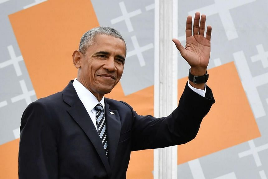 Former US president Barack Obama waving as he arrives on stage before attending a discussion with the German Chancellor during the Protestant church day (Kirchentag) event at the Brandenburg Gate in Berlin on May 25, 2017.