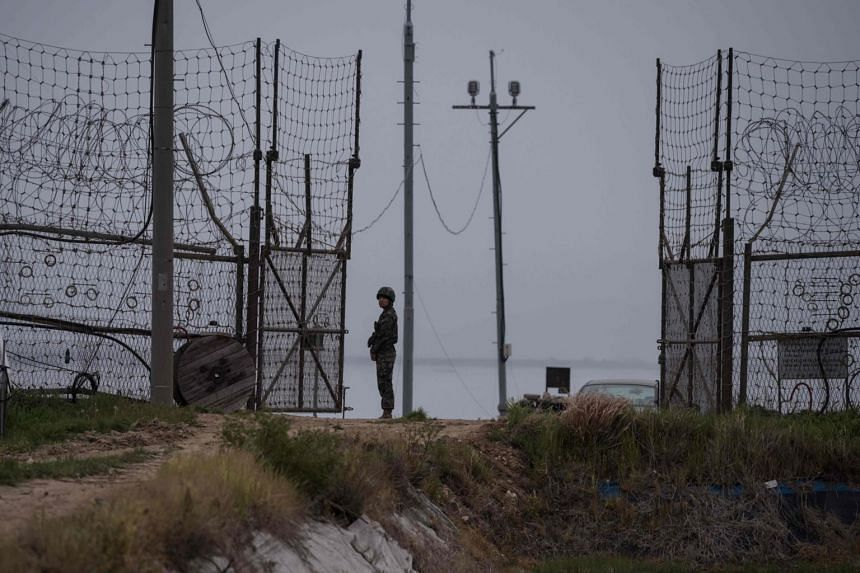 A soldier standing guard at an opening to the fence of the Demilitarized Zone (DMZ) during maintenance, on Gyodong, a tiny outlying island near to the west of Seoul on May 9, 2017.