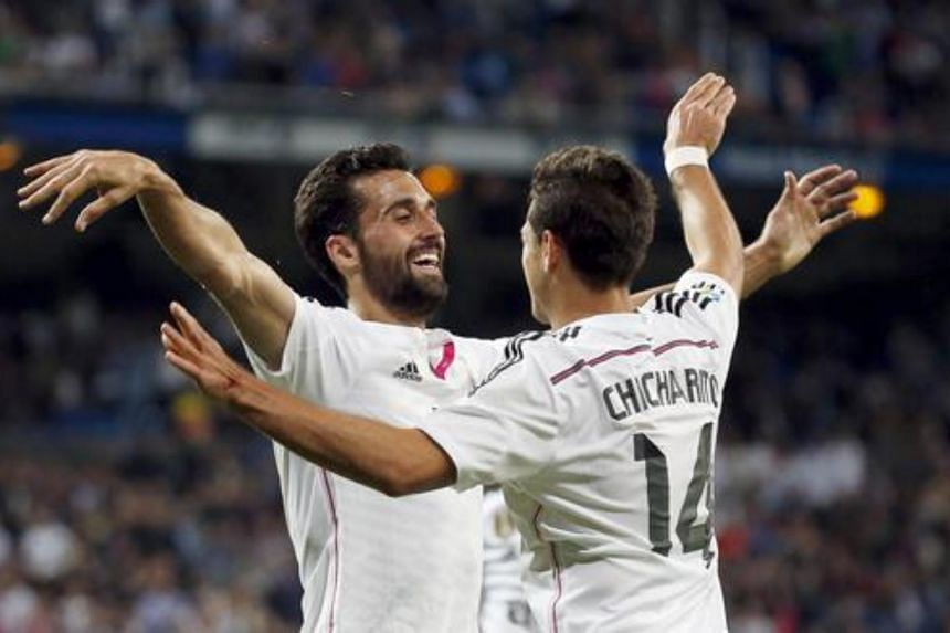 """Alvaro Arbeloa (left) celebrating with team mate Javier """"Chicharito"""" Hernandez after scoring a goal against Almeria during their Spanish first division soccer match at Santiago Bernabeu stadium in Madrid, Spain on April 29, 2015."""