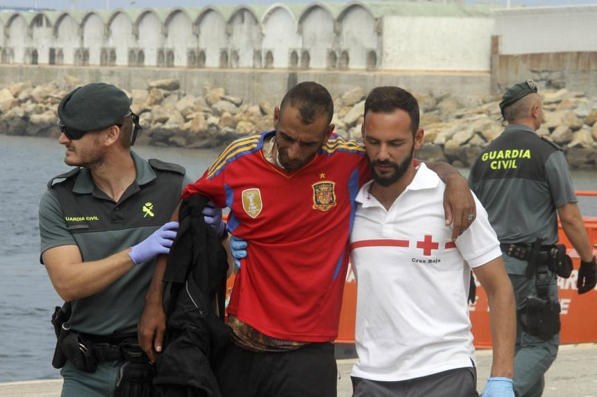 A Spanish Civil Guard and a Red Cross worker helping a migrant who was among a bigger group who were rescued at sea and brought to the port in Tarifa, Spain on June 23, 2017.