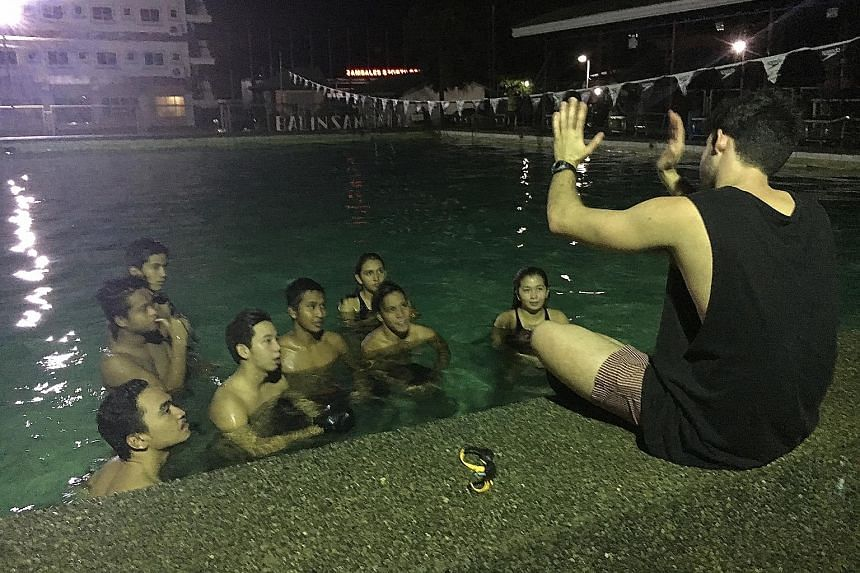 Mr Andrew McLean discussing swimming strategies with the Zambales Swim Team in the Philippines.