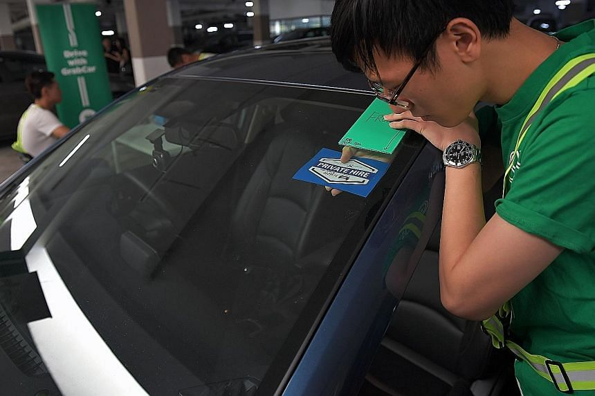 """Above: A Grab employee applying the Private Hire Car Driver's Vocational Licence decal to a car yesterday. About 27,000 cars have had such decals affixed. Left: The word """"void"""" appears on both sides of the tamper-evident decal once it is peeled off,"""