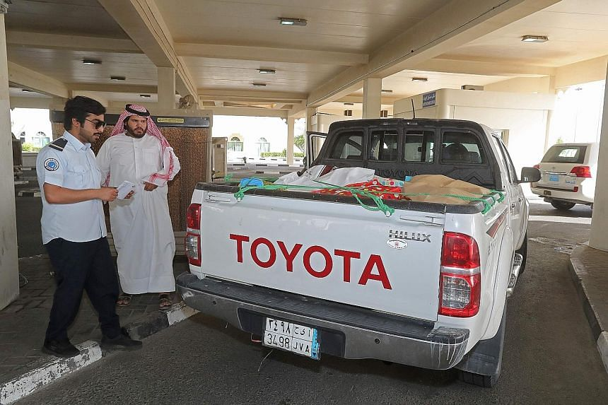 A Qatari official checking a Saudi citizen's vehicle at a border crossing with Saudi Arabia yesterday. A Saudi alliance has severed diplomatic and transport links with Qatar.