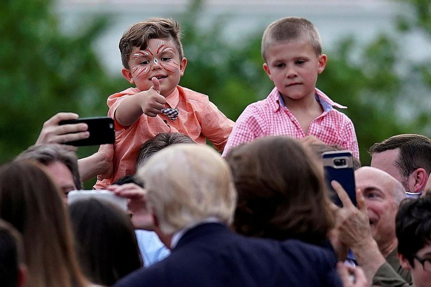 US President Donald Trump (his back facing camera) greeting members of the Congress and their families at a congressional picnic event at the White House on Thursday.