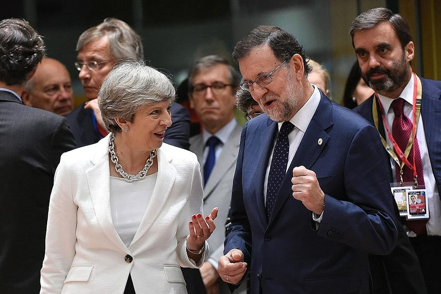 British Prime Minister Theresa May talking to her Spanish counterpart Mariano Rajoy during a European Council meeting in Brussels yesterday, the second day of a summit of European Union leaders.