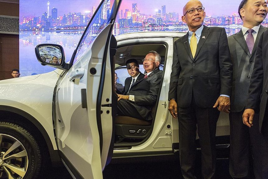 Malaysian Prime Minister Najib Razak (seated in vehicle), DRB-Hicom chairman Mohd Khamil Jamil and Zhejiang Geely group chairman Li Shufu at the signing of the agreement yesterday in Kuala Lumpur.