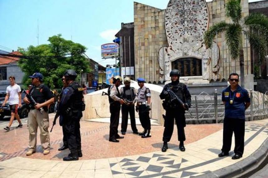 Indonesia police stand in front of the monument dedicated to those killed in the 2002 Bali bombing in the tourist district of Kuta on Jan 22, 2016.