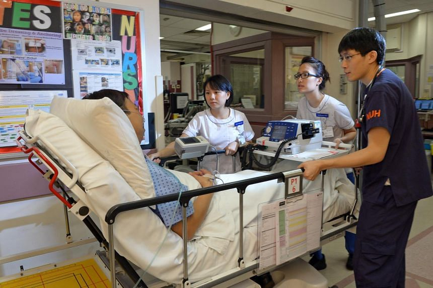 National University Hospital staff nurses and doctor moving a patient for a procedure to explore blockage of heart blood vessels.
