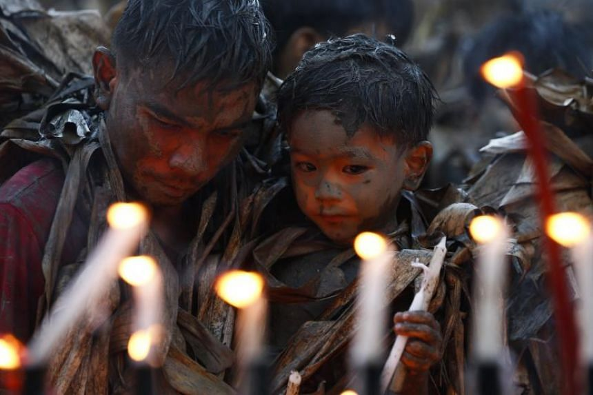 Filipino Catholic devotees covered in mud and leaves light candles outside a church in a Bibiclat village of Aliaga town in northern Philippines, on June 24, 2017.