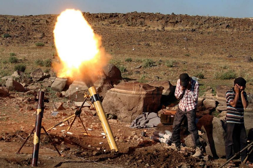 Rebel fighters fire mortar shells towards forces loyal to Syria's President Bashar al-Assad in Quneitra province, bordering the Israeli-occupied Golan Heights.