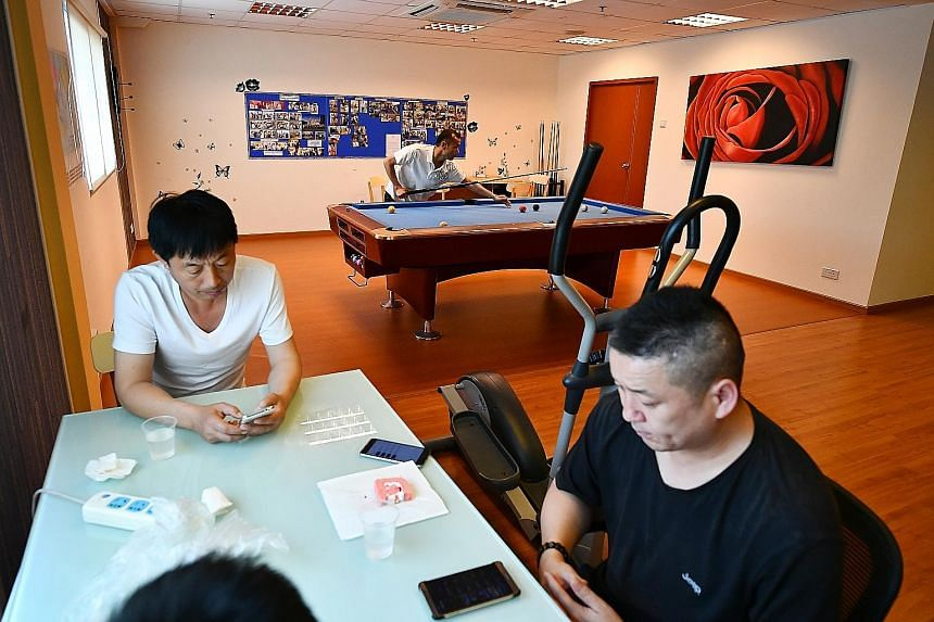 The Maritime House in Tanjong Pagar has serviced apartments for seafarers to stay in, regardless of whether they are here for work or play. Left: Electrician Zhao Yuting (far left), 52, and Captain Chen Guang Ming, 47, surfing the Internet on their c
