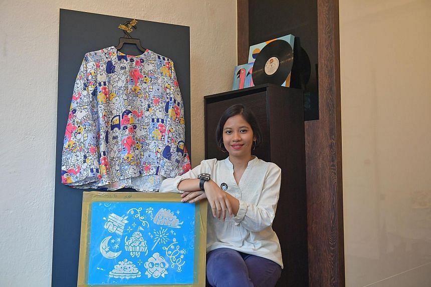 Ms Nur Aida Sa'ad's outfit and card designs feature familiar images such as families chatting away together and Aidilfitri goodies.