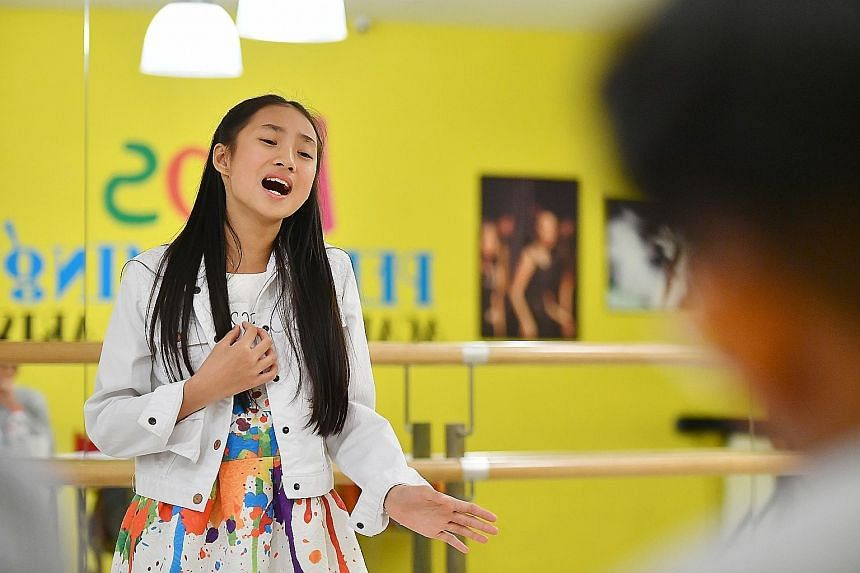 Above: Yumi Chung, 10, from Hong Kong, singing during last Friday's ChildAid audition. Left: Sharon Huang playing the flute. She hopes to make the cut so her family can watch her perform. (From left) Fevrier Eunike Wewengkang, Tesalonika Purba, Adela